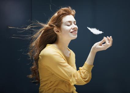 white feather floating into woman's hands