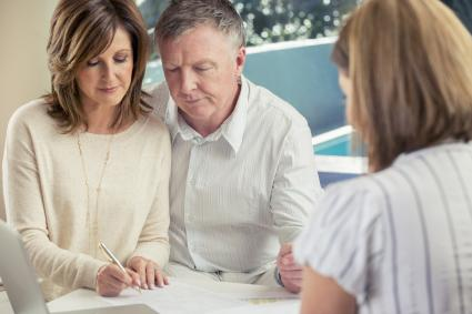 Man and woman signing wills with lawyer