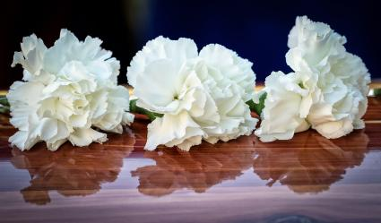 White Carnations sit on a cedar coffin
