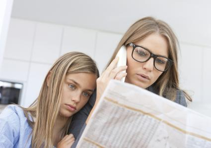 Mother and daughter reading newspaper and making a phone call