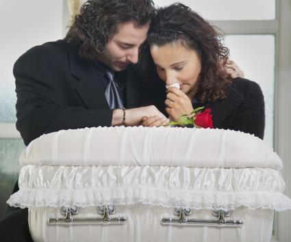 Parents grieving over infant casket