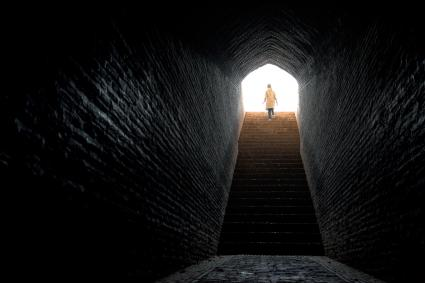Woman timidly stepping into bright light coming out from dark tunnel