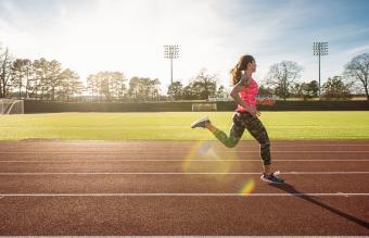 Joven atleta femenina corriendo en la pista