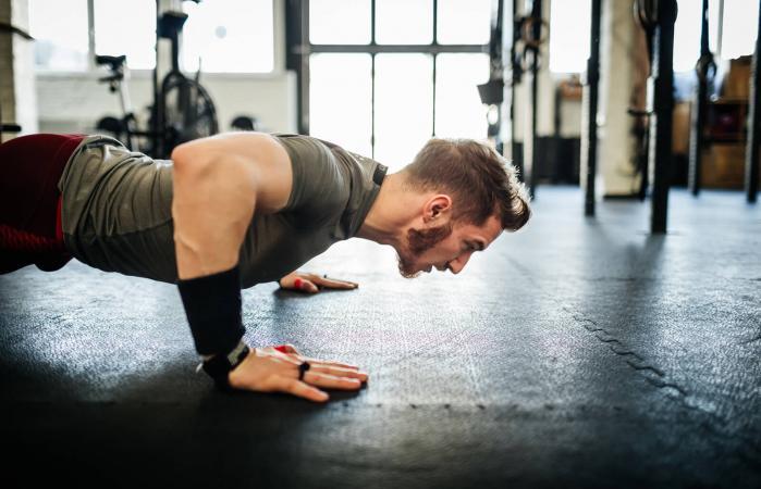 Hombre haciendo flexiones en el gimnasio