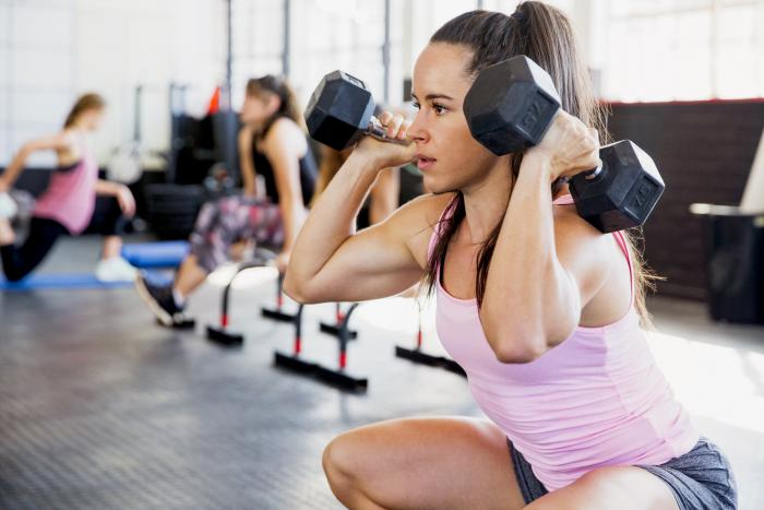 Mujer en el gimnasio haciendo sentadillas con pesas
