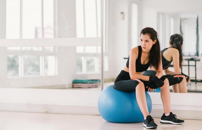 Mujer con pelota de fitness en el gimnasio