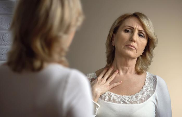 Mujer infeliz mirándose en el espejo