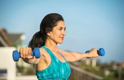 Mujer levantando pesas al aire libre
