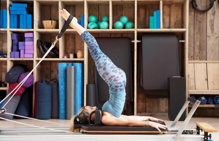 Mujer se estira sobre pilates reformador