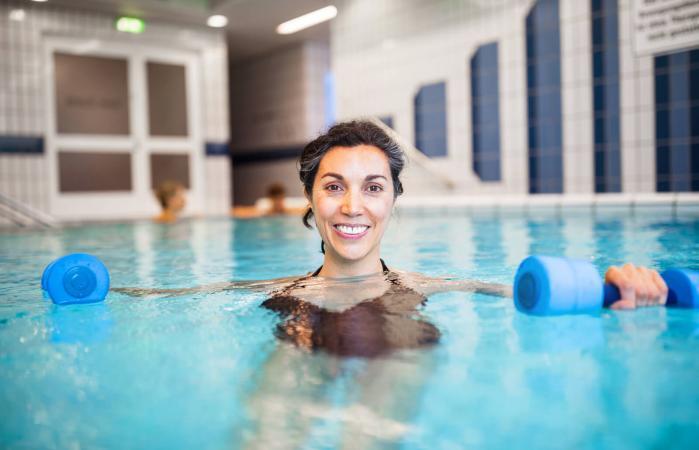 Mujer haciendo ejercicio con mancuernas en la piscina