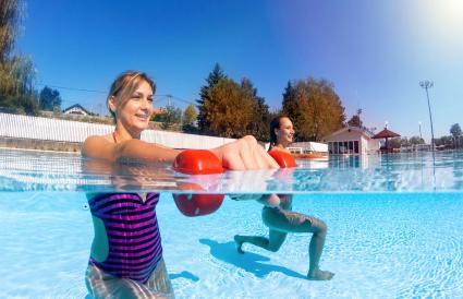 Mujeres haciendo ejercicio con mancuernas en la piscina