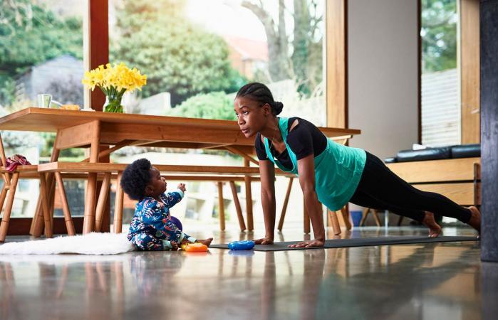 Bebé asistiendo a la madre en el ejercicio