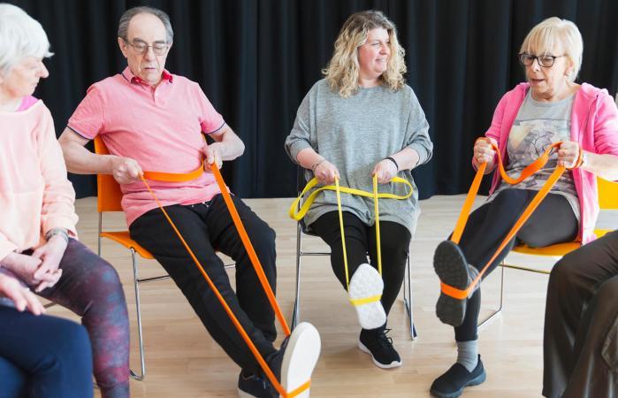 Grupo de personas mayores ejercitando las piernas