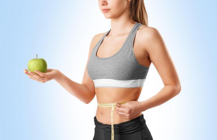 Mujer joven midiéndose la cintura