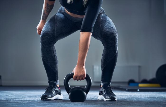 mujer haciendo ejercicio con kettlebell en el gimnasio