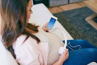 Mujer que usa los auriculares sobre su vientre embarazado