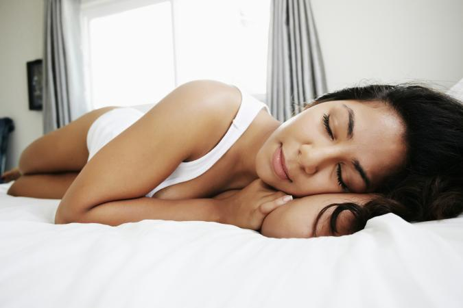 Hispanic woman lying on bed