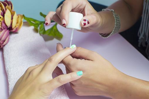 pintando sus uñas rojas