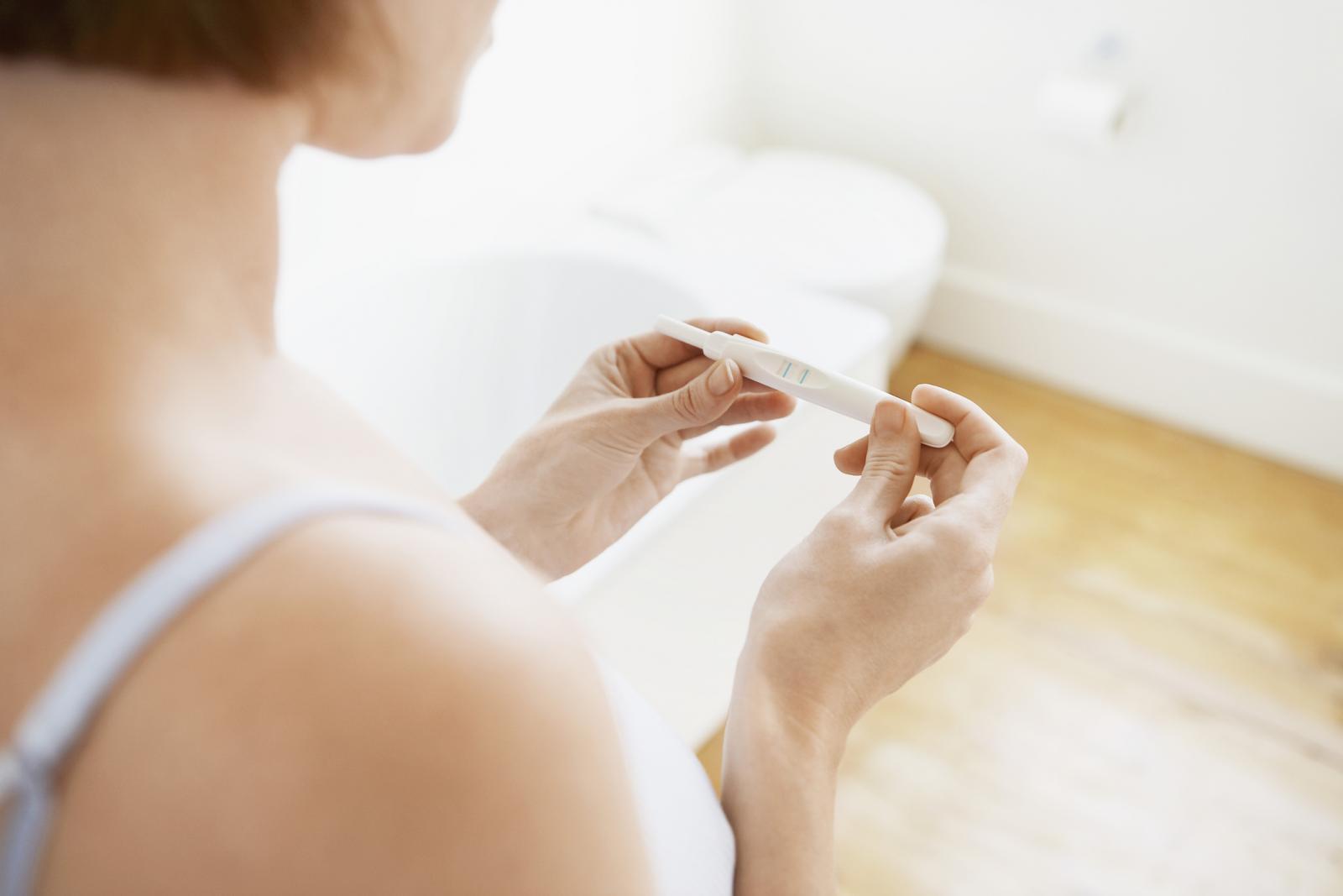 Una mujer con una prueba de embarazo