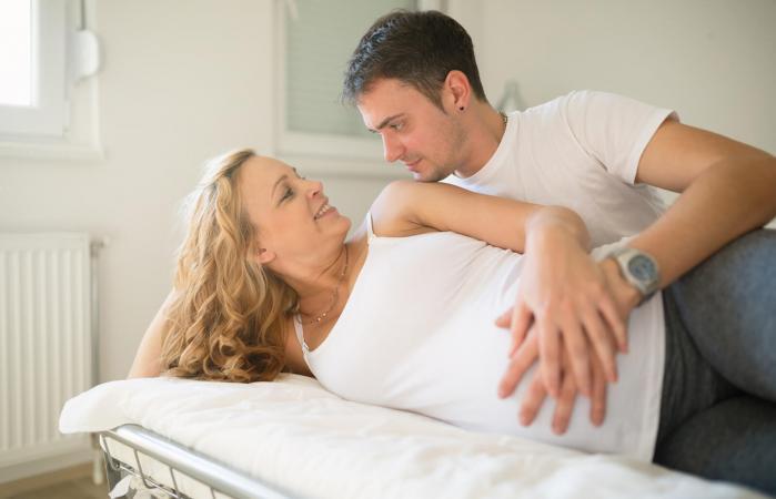 Pareja embarazada en la cama
