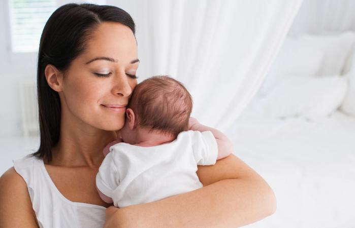 Madre sonriente con bebé recién nacido