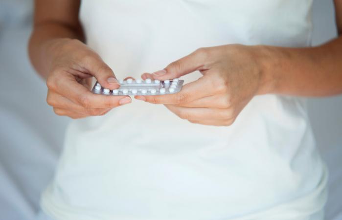 Mujer con pastillas anticonceptivas en la mano