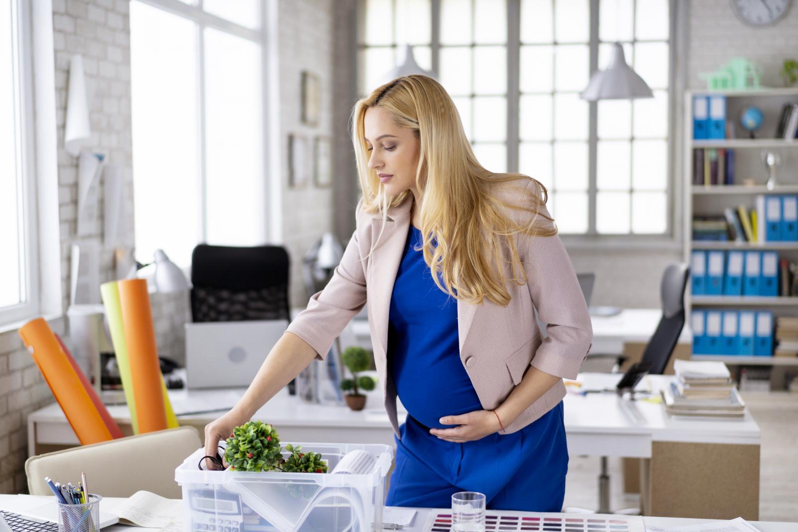 Mujer embarazada dejando el local de trabajo