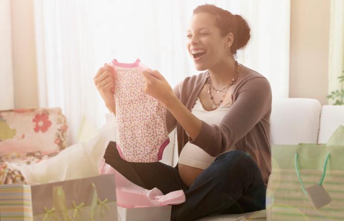Mujer embarazada abriendo regalos en el baby shower