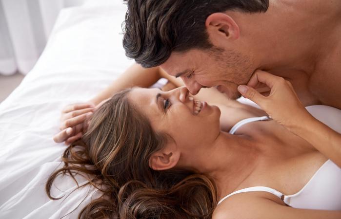 Joven pareja cariñosa en su cama