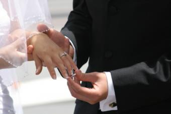 Putting on wedding band above engagement ring during ceremony