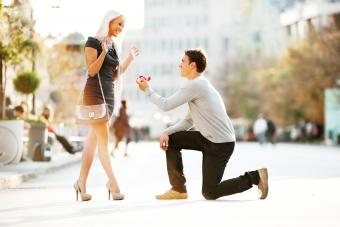 Young man proposing on bended kneee