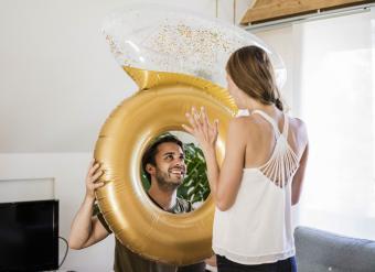 Smiling man looking at girlfriend through large inflatble ring