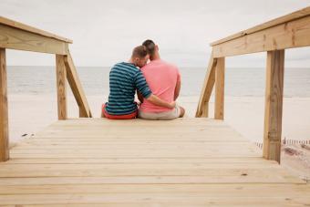 couple sitting on boardwalk against sea