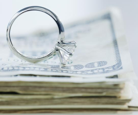 Wedding ring on stack of cash