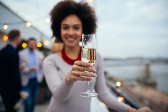 Woman raising champagne toast, glass focus