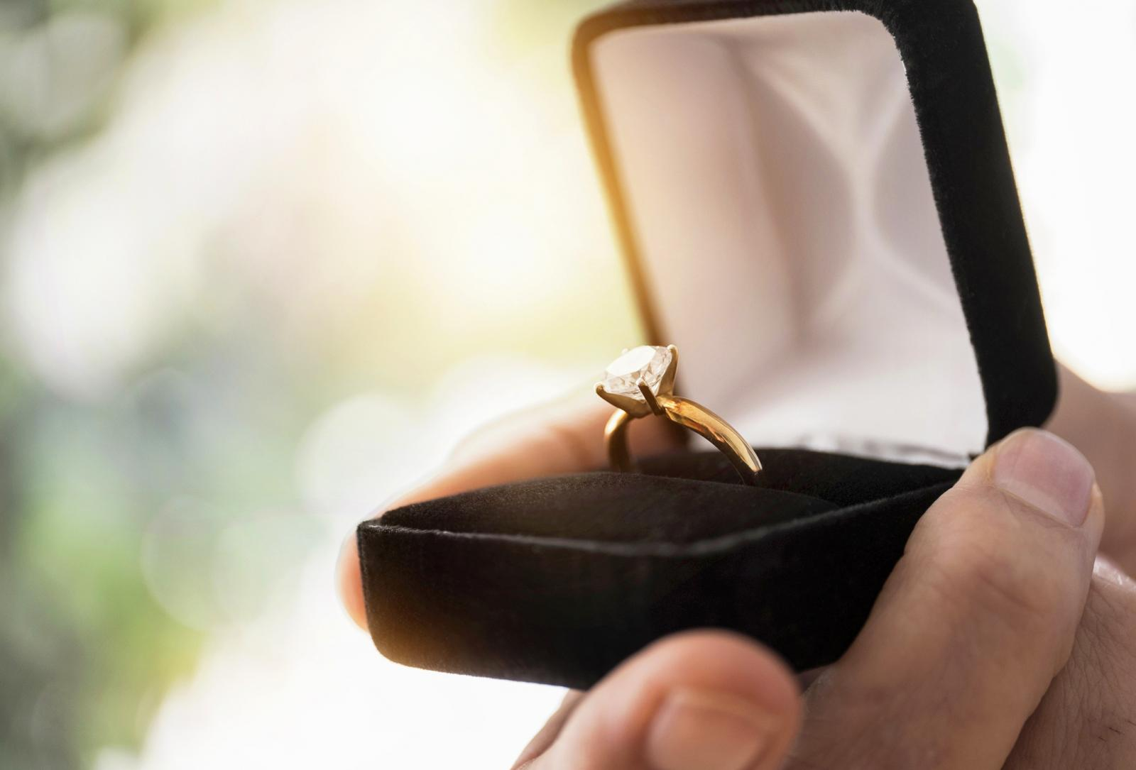 Mans hand holding open box with engagement ring