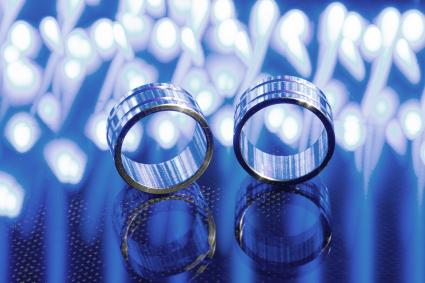Two wedding rings surrounded blue lights on a reflecting surface