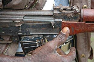 Image of a man's hand on a rifle