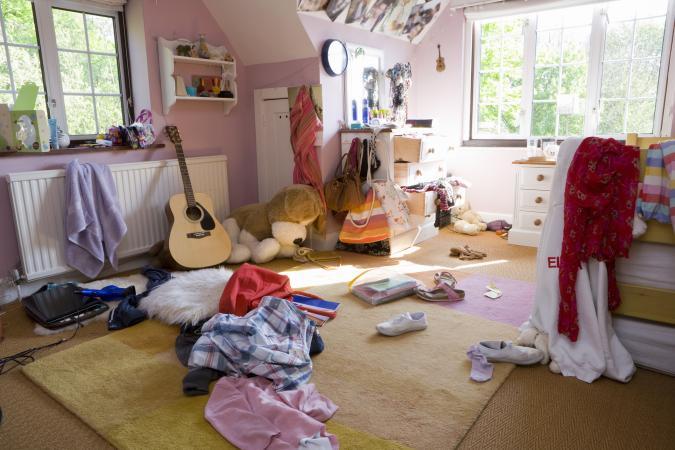 Dormitorio desordenado con ropa en el piso