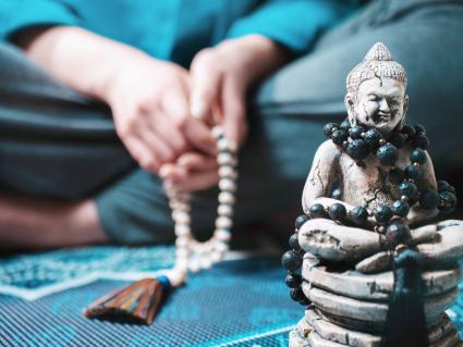 Buddha Figurine Against Woman With Beads Sitting On Carpet