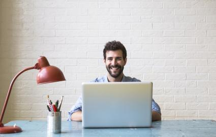 Hombre feliz sentado en su escritorio con un portatil