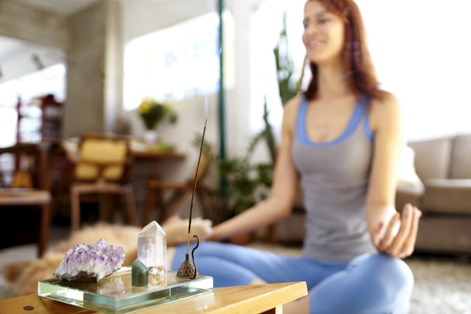 Mujer haciendo yoga en una habitación con incienso y cristales