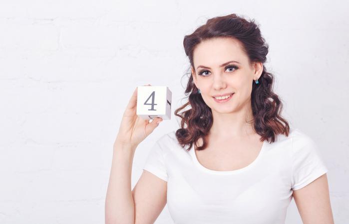 Chica sosteniendo el número cuatro
