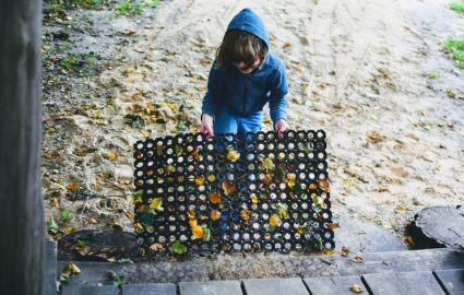 niño sosteniendo una estera de puerta