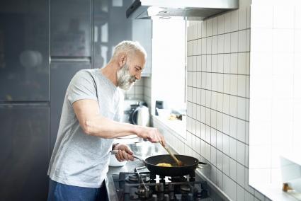 Hombre cocinando en su cocina blanca y gris