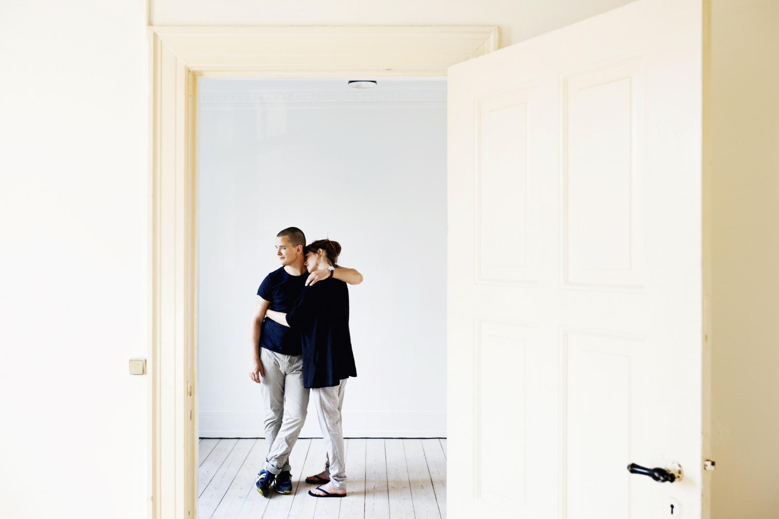 Pareja abrazandose en la entrada del piso