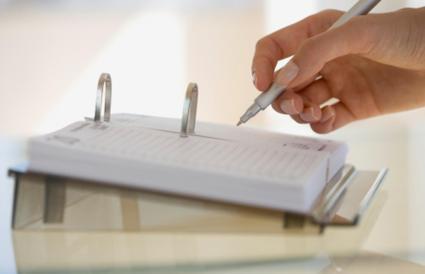 Mujer escribiendo en el calendario de escritorio