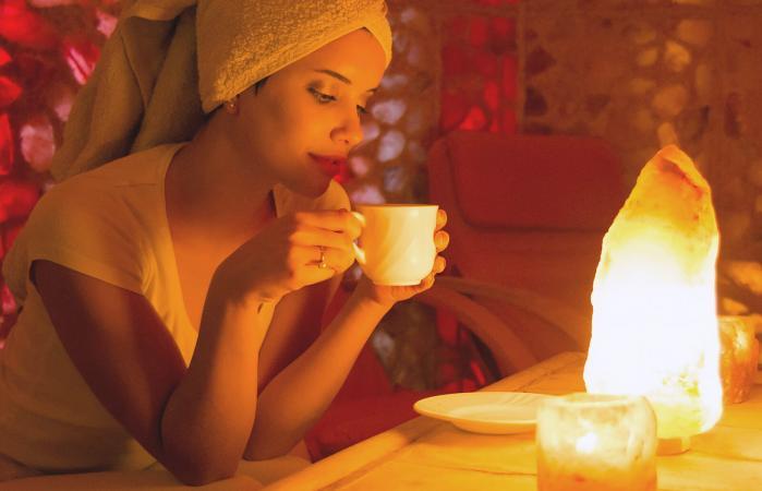 Mujer bebiendo té frente a una lámpara de sal