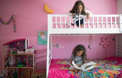 Niñas hermanas jugando y leyendo libros en una litera