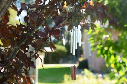 Campana de viento de metal colgada en un árbol